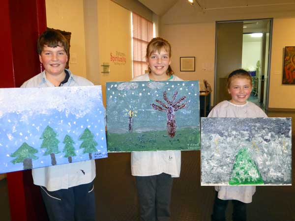 three children holding up paintings
