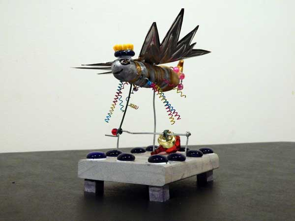 A flying animal made out of various craft items including multicoloured springs