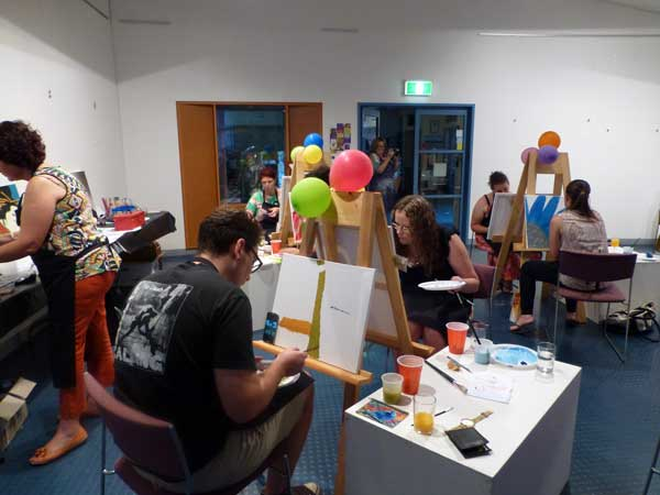 people painting coloured balloons on easels