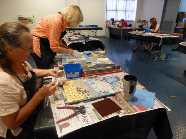 Two ladies making mosaics