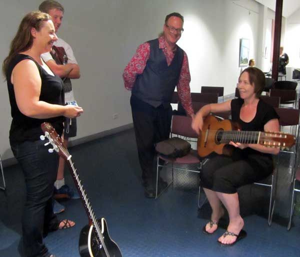 Matthew Fagan teaching guitar to a lady with a couple of onlookers