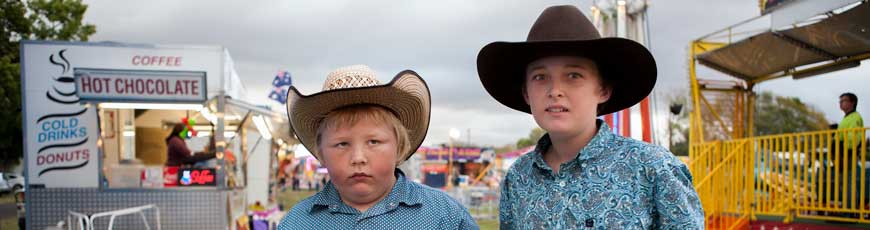 Two boys with cowboy hats on at a show